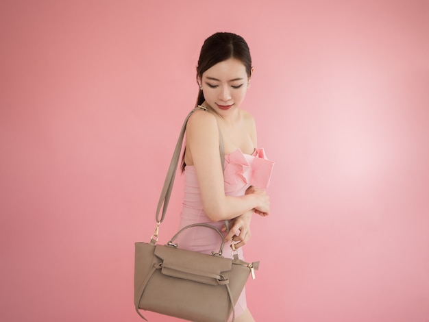 Asian woman looking shoulder bag, sexy girl show hand bag on pink background