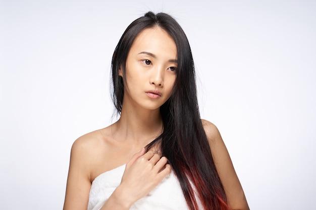 アジアの女性は体の裸の肩の衛生にヘアタオルを緩めます