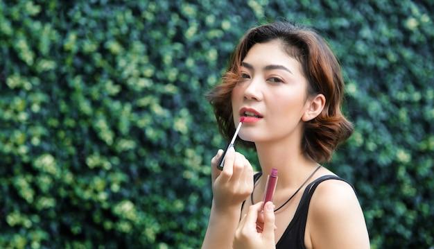 アジアの女性の愛の美しさは屋外の日陰に口紅でメイクアップ