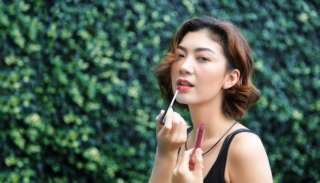 Asian woman love beauty make up with lipstick on outdoor shade