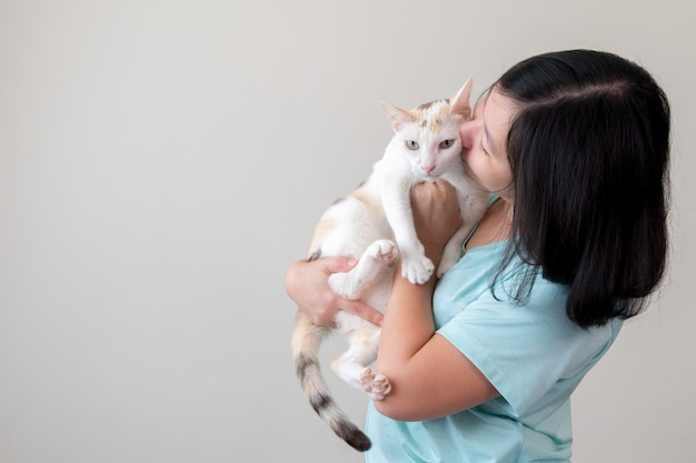 An asian woman lovingly holds a cat and kisses it.