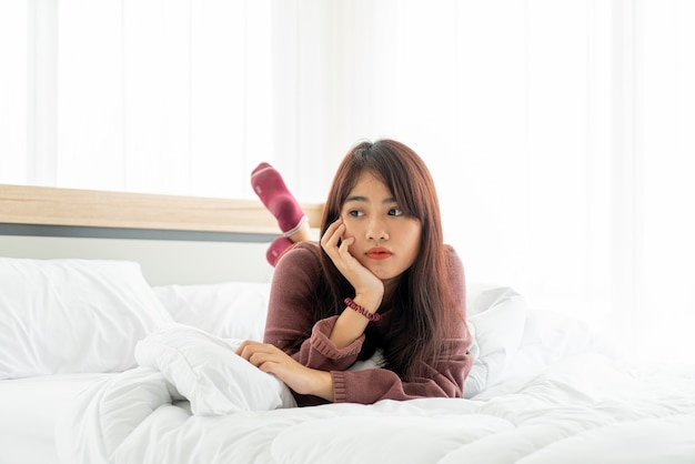 Asian woman lying on bed in the morning