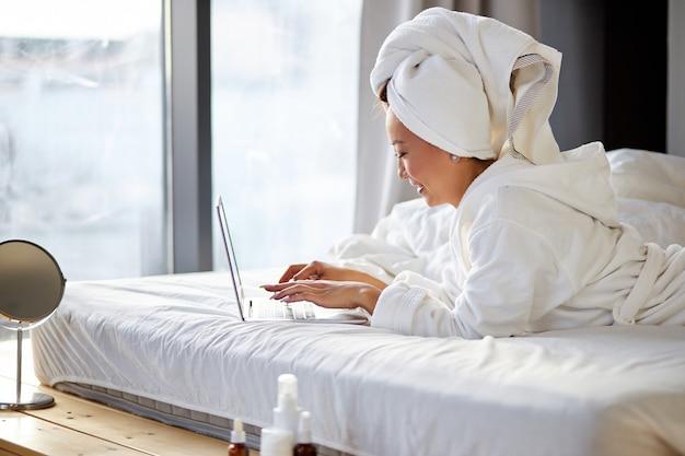 朝、自宅のベッドに横になり、ラップトップコンピューターで作業し、タオルとバスローブを着ているアジア人女性。在宅勤務、検疫コロナウイルスの概念