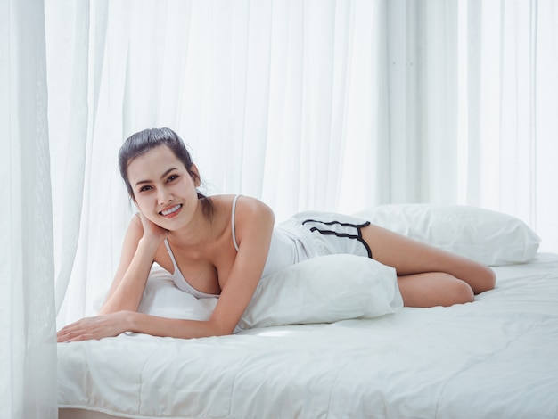 Asian woman lying in white bed
