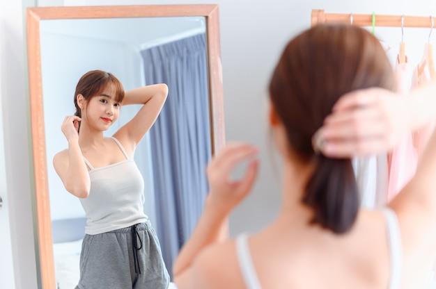 アジアの女性は自宅でメイクアップとドレスアップ。寝室でのライフスタイル。社会的距離と自己検疫。