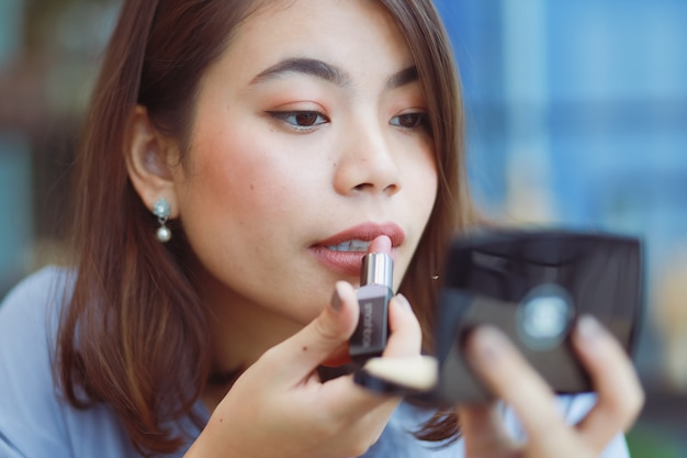 Asian woman make up her face with lipstick in cafe