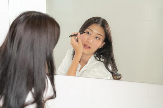아시아 여자 거울을보고 자신을 만들어