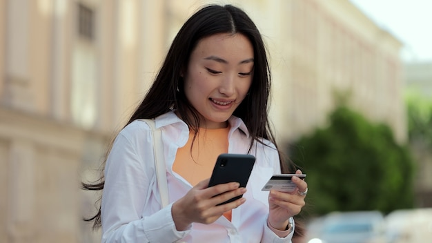 Asian woman makes online payments through the internet from bank card on smartphone student girl on street with credit card and phone woman celebrating a successful purchase