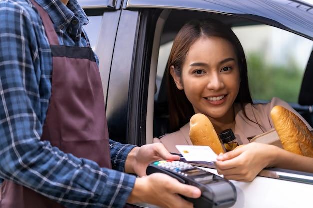 Азиатская женщина делает бесконтактный платеж за продуктовый