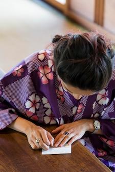 일본 종이로 종이접기를 만드는 아시아 여성