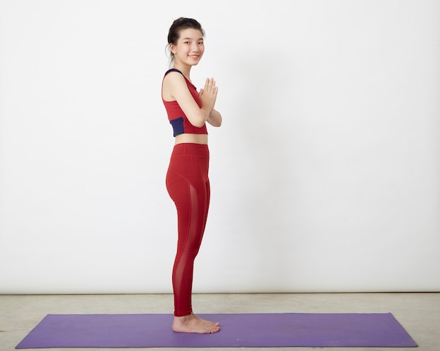 Азиатская женщина делает позу на коврике для йоги, тренируясь в студии