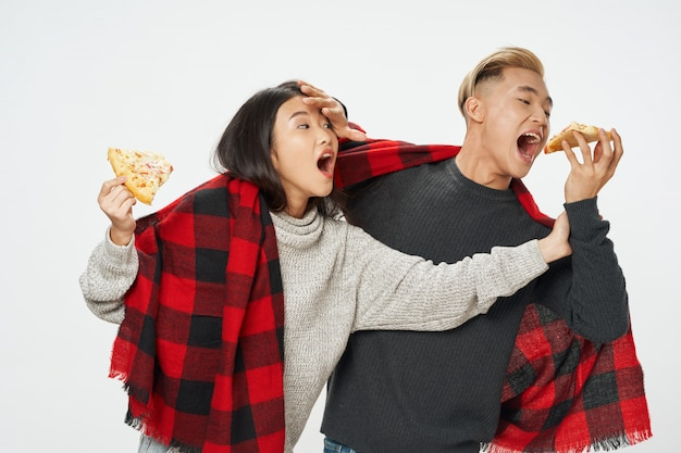 Asian woman and man eating pizza