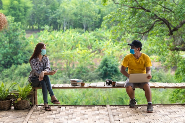 Asian woman and man in social distancing sitting on bench in the middle of nature, social distancing concept.