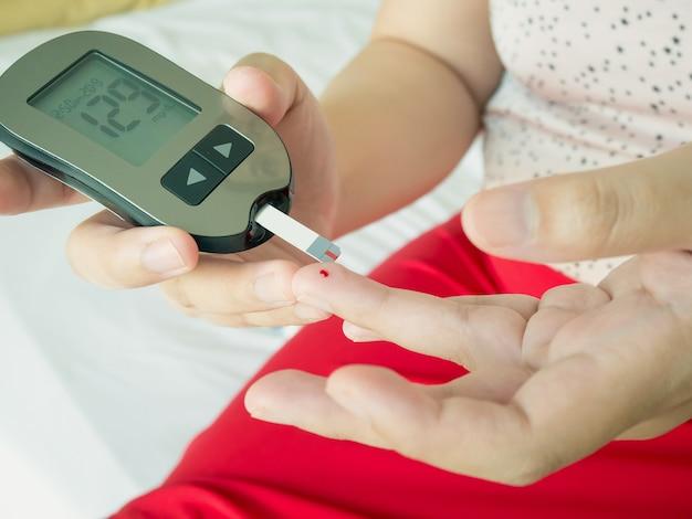 アジアの女性がデジタルグルコースメーター、糖尿病テストでグルコースレベルを測定