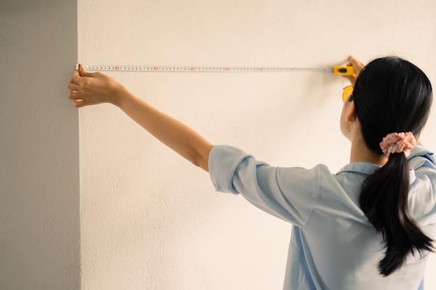 壁のサイズを測定するアジアの女性