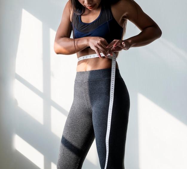 Азиатская женщина, измеряющая размер талии