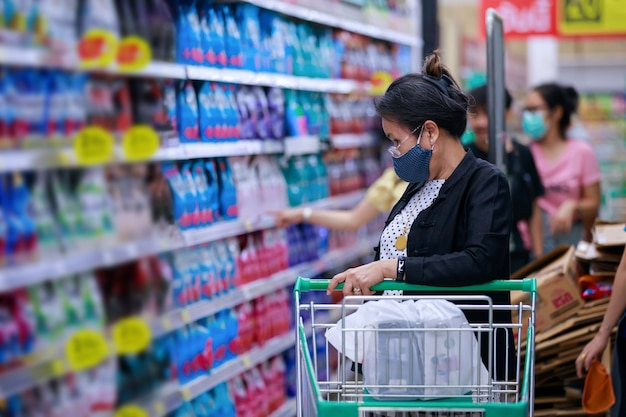 Asian woman in medical protective mask with a basket walks in a supermarket
