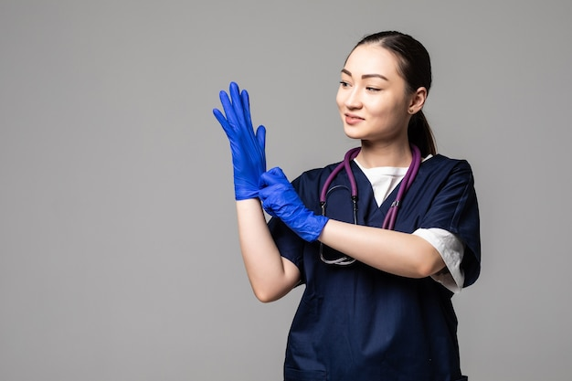 Asian woman in medical uniform and face mask wearing protective gloves isolated over white wall