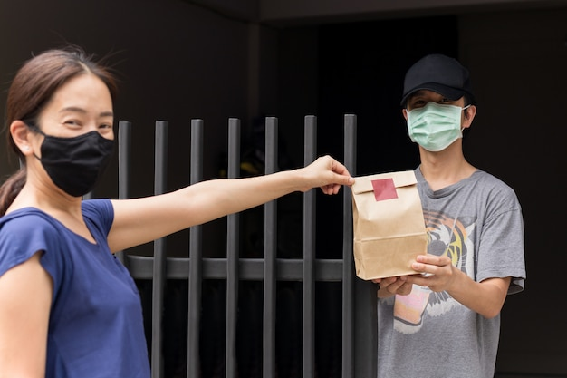Asian woman and men wearing protective mask brown bag