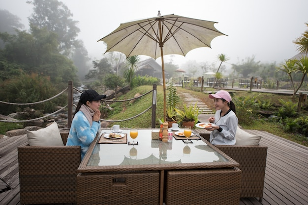 Asian woman at morning breakfast table.