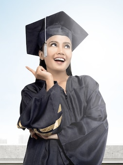 Asian woman in mortarboard hat graduating from college