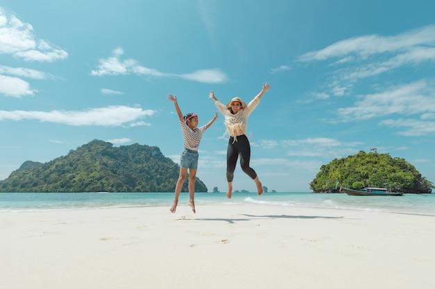 아시아 여자 어머니와 딸이 공중에 점프와 해변에서 놀고 함께 아름다운 자연과 함께 즐기는. 여름 휴가 및 가족 여행 개념.