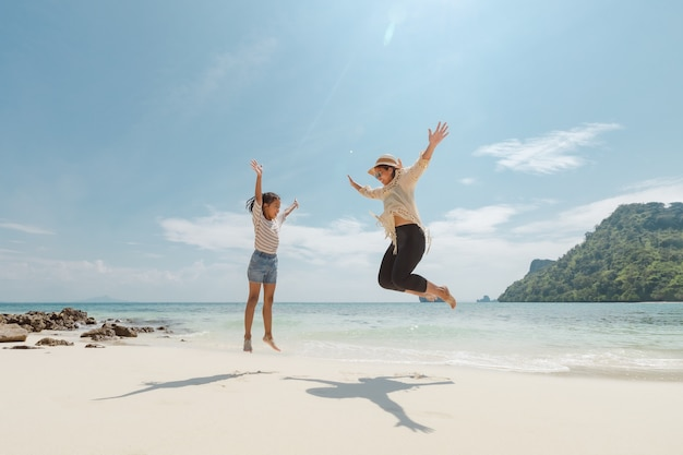 Asian woman mother and daughter jumping up to the air and playing on the beach and enjoying with beautiful nature together. summer holidays and family trip concept.