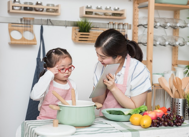 Asian woman mother and daughter play together in kitchen,mom hold tablet for teach little girl how to cook in semester break