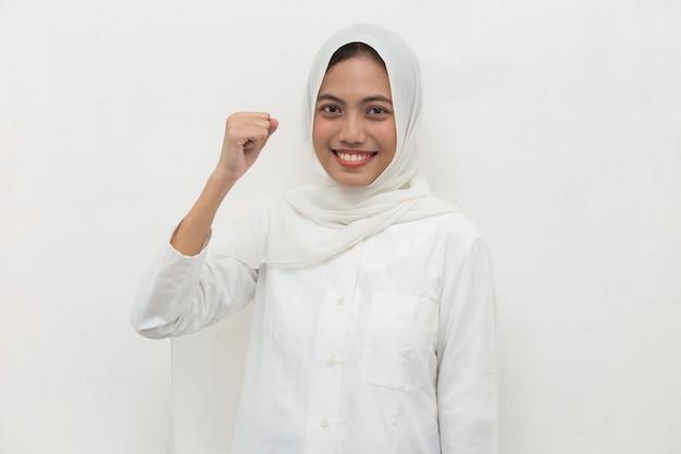 大きな成功の力のエネルギーと前向きな感情を表現する勝利を祝う幸せで興奮しているアジアの女性イスラム教徒