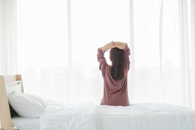 Азиатская женщина на кровати и просыпаться по утрам