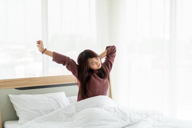 ベッドの上のアジアの女性と朝目を覚ます