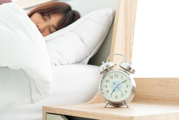 ベッドの上で朝起きているアジアの女性
