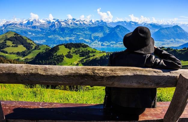 Азиатская женщина на скамейке с видом на швейцарский rigi kulm