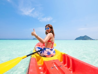 Asian woman on the kayak boat in Andaman blue sea and blue sky background