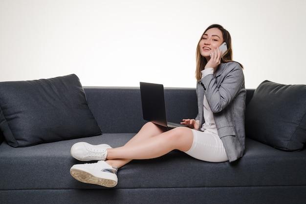 居間で自宅でラップトップを使用して電話でアジアの女性。検疫封鎖で自宅で仕事をしています。
