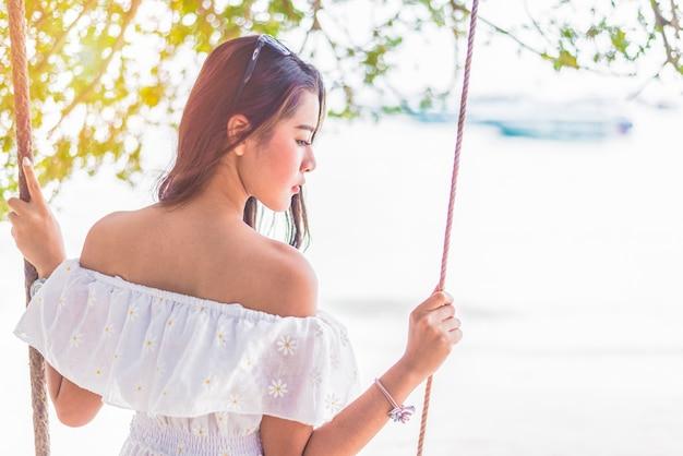 ビーチでスイングに座っている白いドレスにアジアの女性