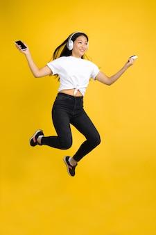 黄色の背景、感情のアジアの女性