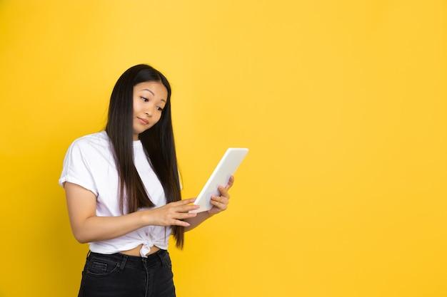 黄色の壁にアジアの女性、感情
