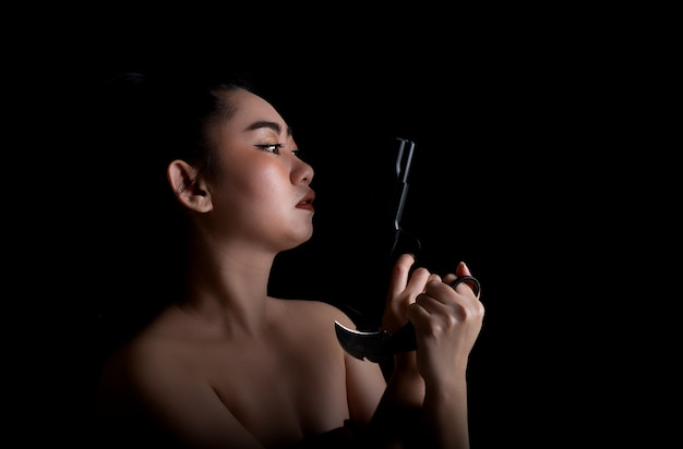 Asian woman one hand holding a gun and karambit knife on black