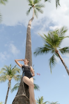 Asian woman in one piece swimsuit posting with coconut palm tree in tropical beach