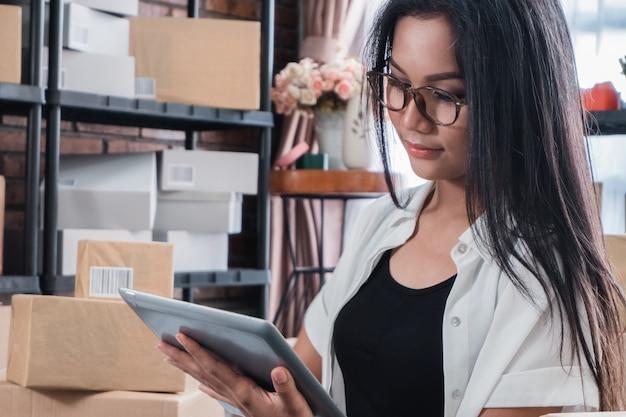 Продавец азиатской женщины онлайн используя таблетку