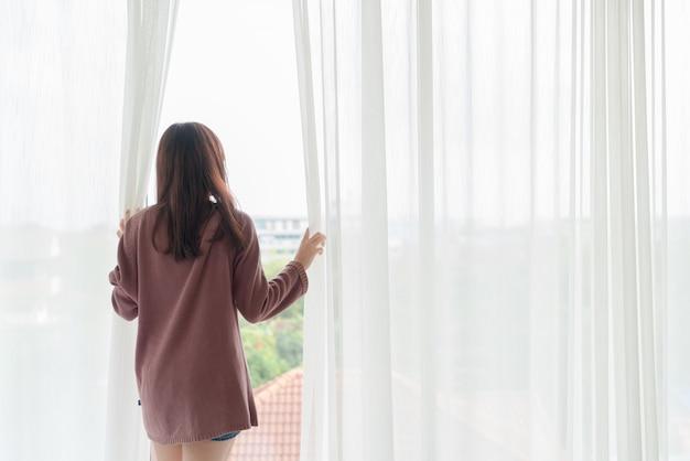 Азиатская женщина открывает занавес утром