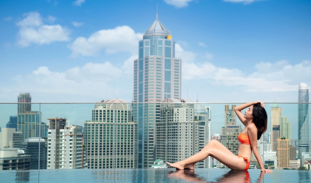 Asian woman in orange swimsuit relax in rooftop swimming pool with bangkok city