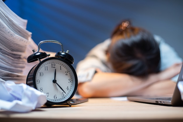 Asian woman overwork and sleep on the table after she feeling very try.depression and anxiety.chinese office girl sleeping after can not find data and solution to do her report.workaholic people.
