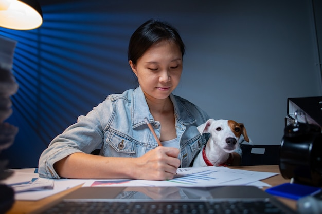 Азиатская женщина-владелец, работающая сверхурочно со своей собакой дома. джек-рассел-терьер, интересная рабочая зона. проверка отчета по документу. работа из дома.