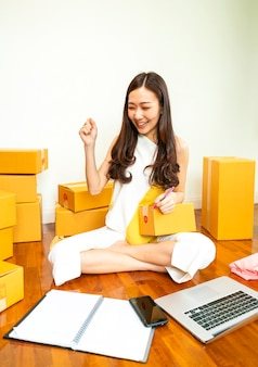 Asian woman packing box for her online market customer