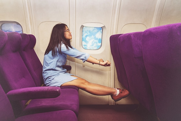 Asian woman passenger relaxing at the business class of airplane