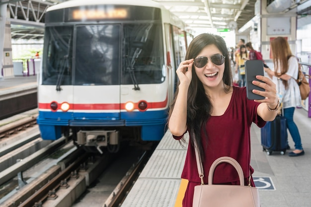 Asian woman passenger with casual suit taking selfie by the mobile phone