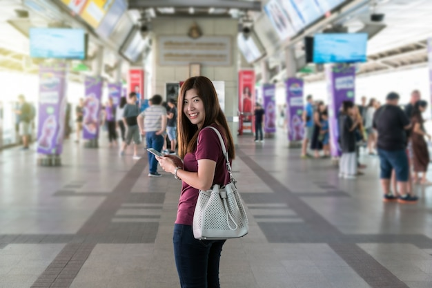 Asian woman passenger with casual suit using the smart mobile phone at the interexchange between sta