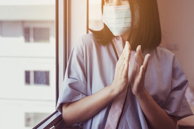病院の窓の近くでコロナウイルスcovid-19と戦う人々を支援するために拍手するアジアの女性患者